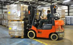 Forklift truck in warehouse. Pallet racking protectors help prevent forklifts damage to racking