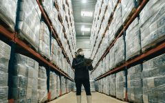 Man in mask wit clipboard between pallet racking